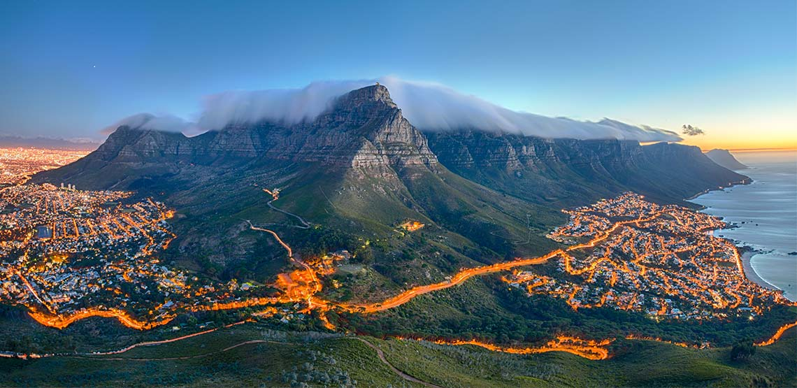 Table Mountain looms over Cape Town on Africa's southwest coast, its peaks swaddled in clouds as lights blaze in the city below.