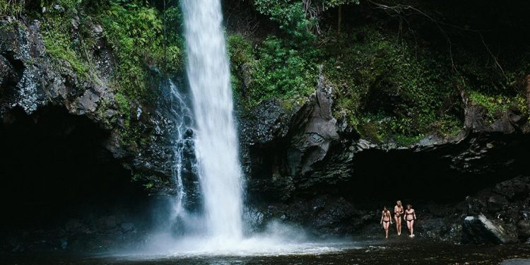 Three women in bathing suits standing by a waterfall.