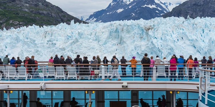 Tourists stand on deck of cruise ship to look at passing glacier.
