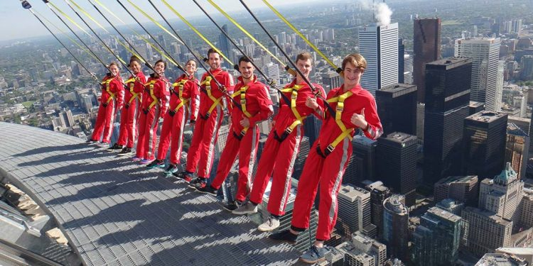 People in red jumpsuits and harnesses leaning over edge of Toronto skyline.