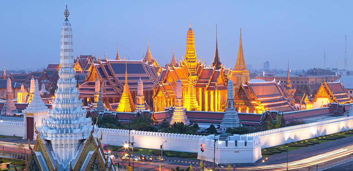 Palace glowing gold with white wall surrounding it.