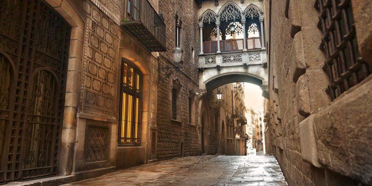 Narrow cobblestone street with Gothic walls.