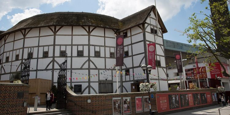 Globe Theatre, a white round building with brown thatched roof.