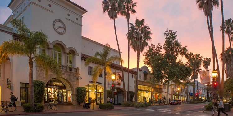 City street with old Spanish style store fronts and palm trees.