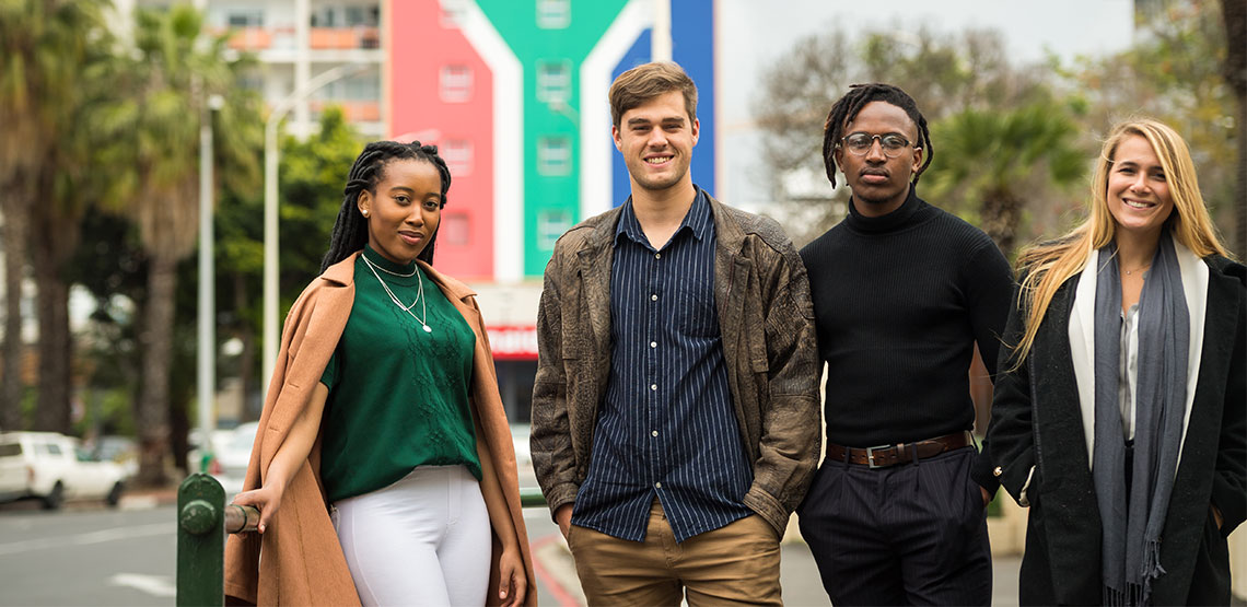 A group of young South Africans pose smiling before a building emblazoned with the colors of South Africa's flag.
