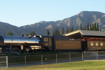 Royal Hudson steam train at a station with mountains in background.