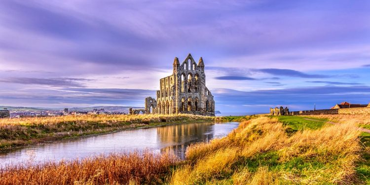 Whitby Abbey, a church in ruins across a river with purple sky