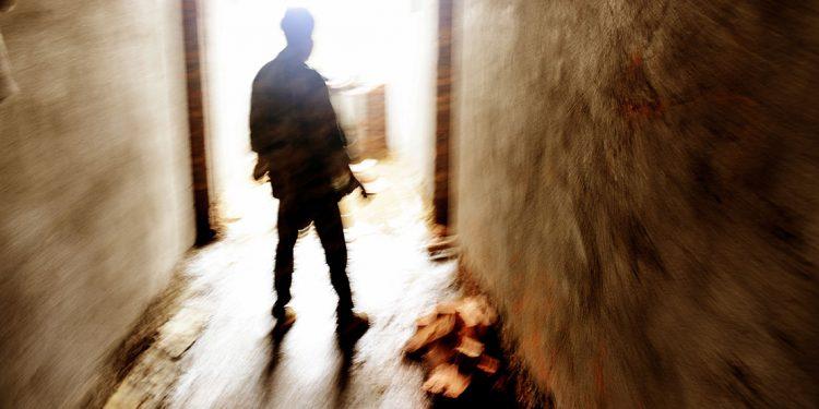 blurred figure standing menacingly in a doorway
