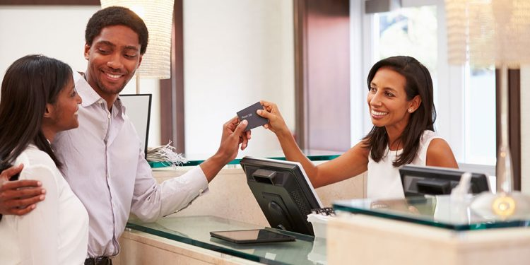 happy couple takes hotel room keys from front desk