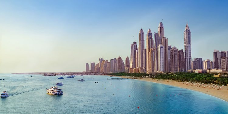 Dubai skyscrapers with beach and yachts.