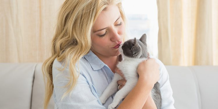 blonde woman holding and kissing a grey and white cat