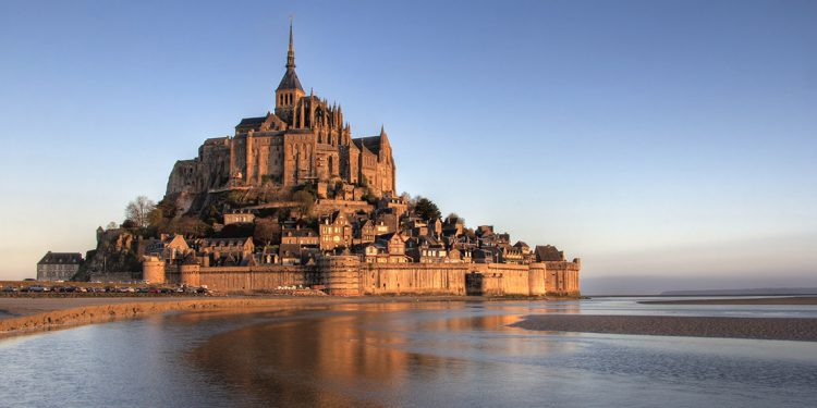 Mont St Michel bathed in the warm glow of a sunset