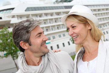 mature couple smiling at each other in front of a cruise ship