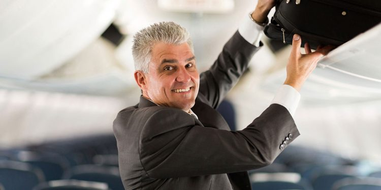 older man putting carry on in the overhead bin of an airplane
