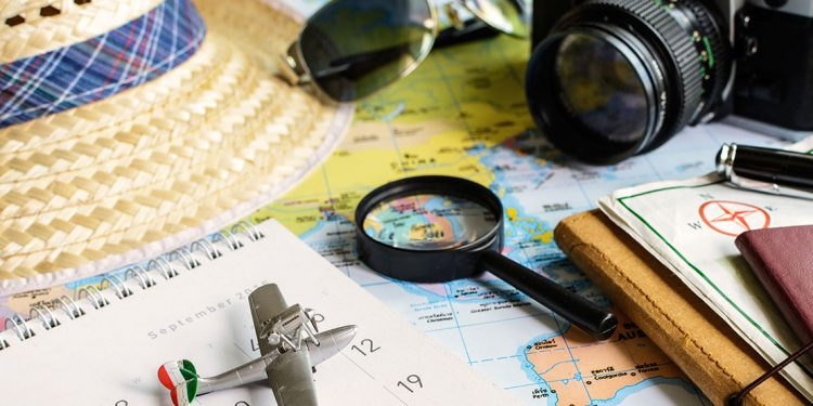 camera, sunglasses, a hat and other travel items sit on top of a map
