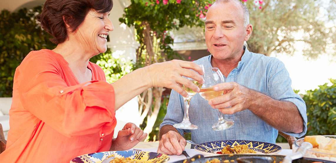 senior couple click glasses of white wine while enjoying a meal