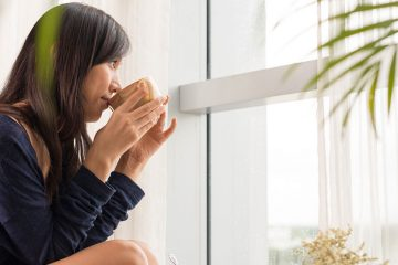 young woman sipping from a mug while looking out a bright window