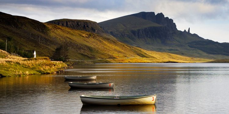 row boats tied to the shore with green Scottish cliffs in the background