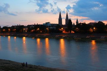 city lights from Szeged reflect in the water at sunset