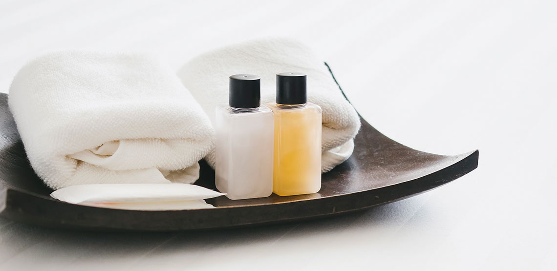 travel sized toiletries and towels on a decorative plate