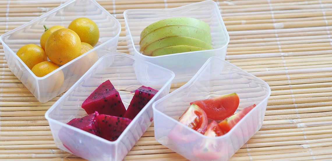 four plastic containers of fruit on a bamboo mat