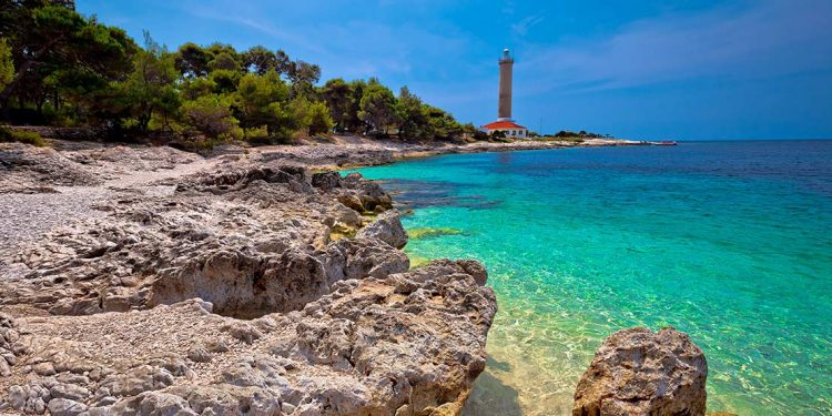 Turquoise waters on rocky coastline with lighthouse in distance.