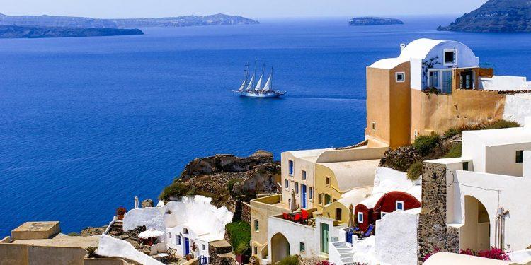 tall ship sets sail on the coastline of Santorini in Greece