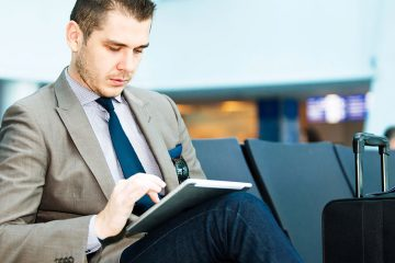 Man sitting at airport terminal on his tablet device