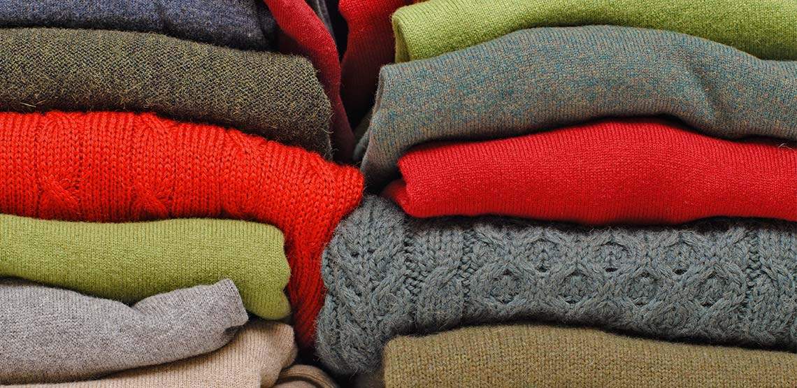 two stacks of knit sweaters in different colors