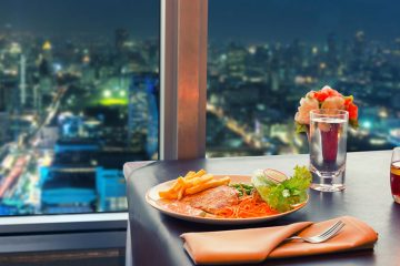 a meal sits on a table overlooking the city at night