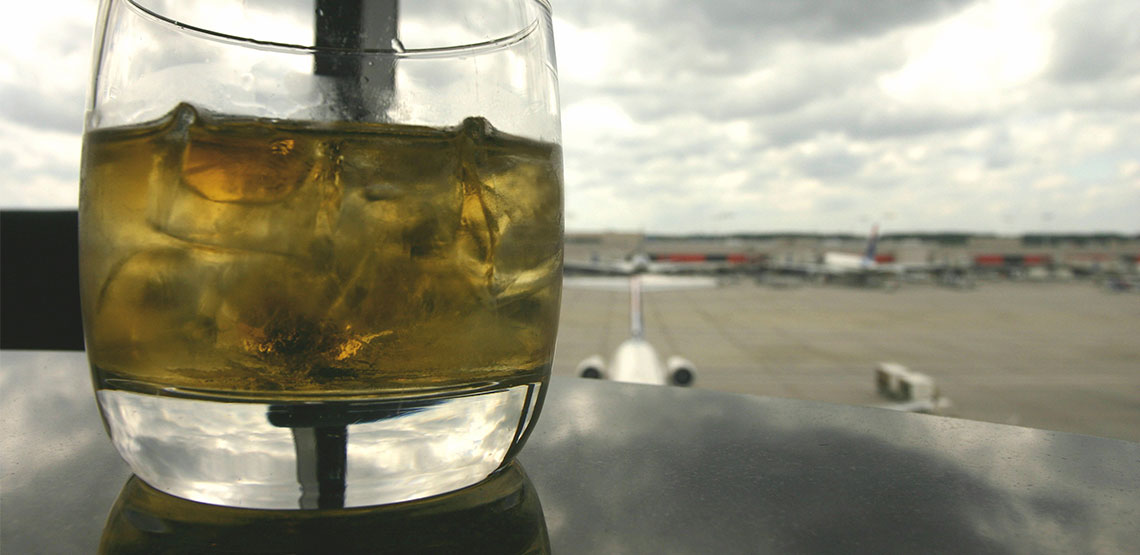 A mixed drink is on a table with a view of an airport runway