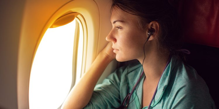 Woman staring out window of plane.