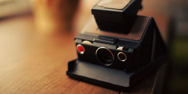 A polaroid camera sits on a wooden table.
