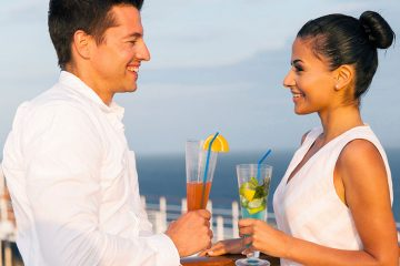 A man and woman look into each others' eyes while enjoying a cocktail on a cruise ship