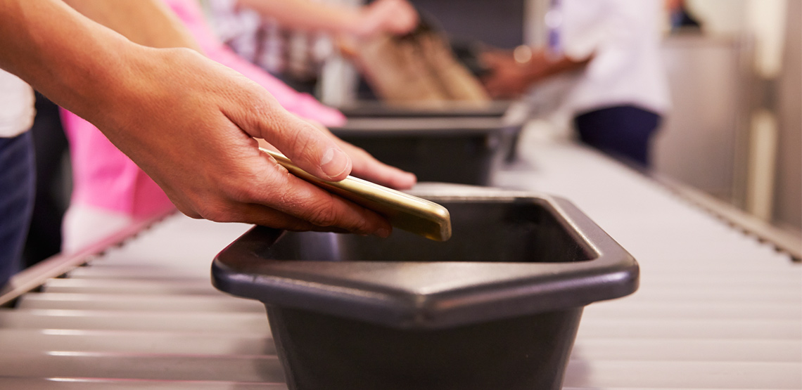 person placing smartphone in TSA check bin in airport security