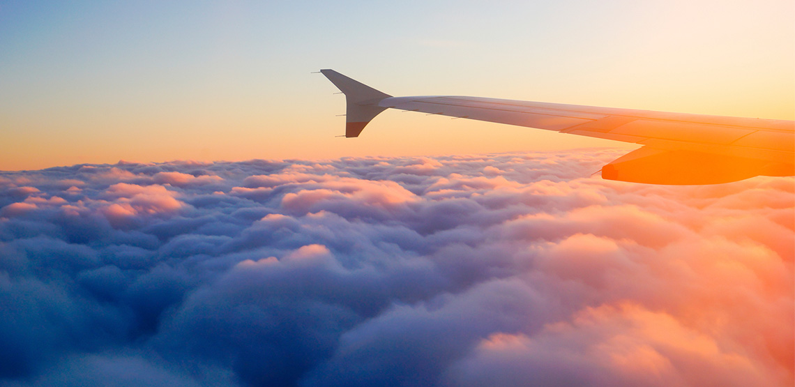 wing of an aircraft above the clouds at sunset