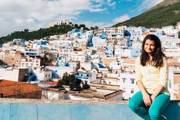 Woman sitting in blue ledge with Moroccan city in background