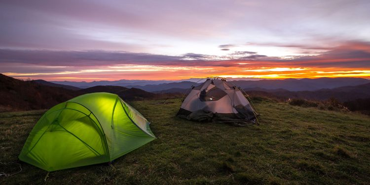 Two tents on rolling mountains during sunset.