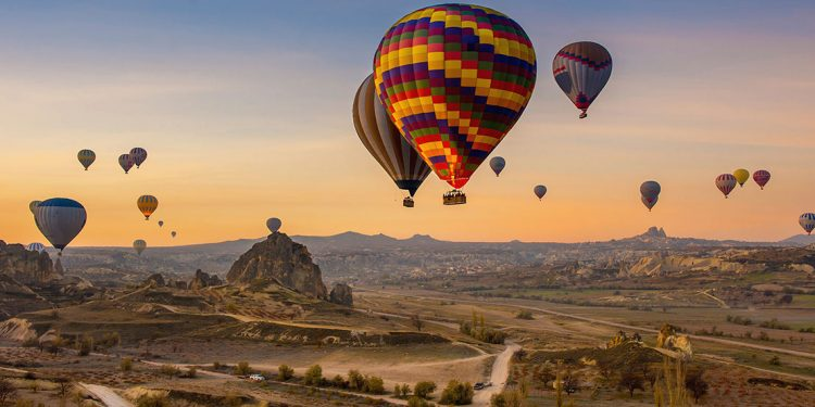 Sunrise over Cappadocia, Turkey with many hot air balloons hovering above the land.
