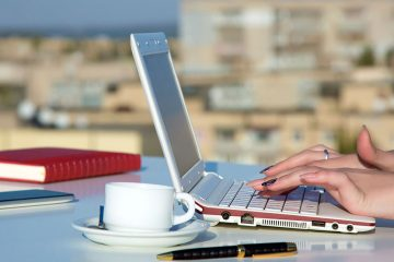 Female hands typing on laptop while sipping a coffee in foreign destination