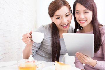 Two smiling women sitting at a cafe table look at an iPad