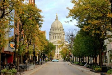 The Wisconsin State Capitol building at the end of a street lined with trees