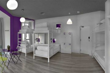 Inside a modern U Hostel room with bunkbeds and purple and white decor