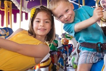 children smiling on merry go round