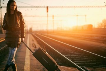 woman with rolling luggage next to train tracks