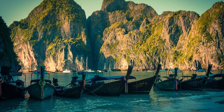 boats surrounded by mountains in maya bay thailand