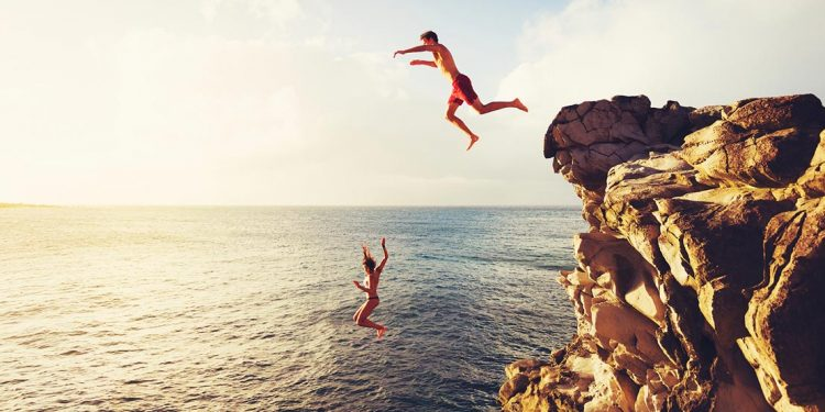 people jumping off a cliff into water