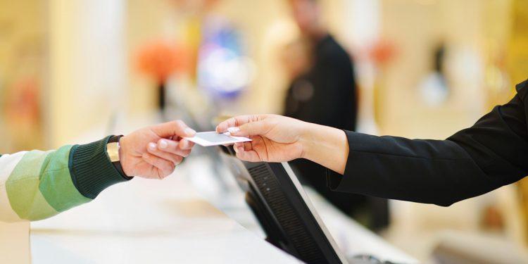 hotel clerk handing room key to guest