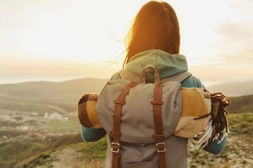 traveler with backpack overlooking mountains