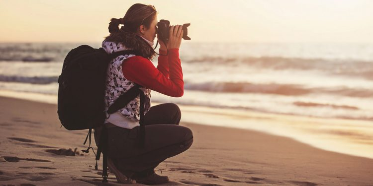 woman taking a photo on the beach